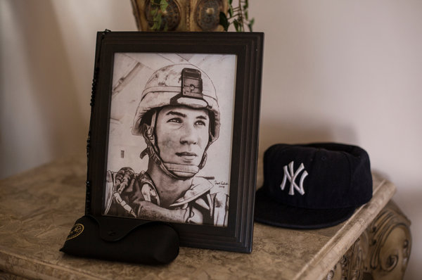 """A portrait of Lance Cpl. Gregory Buckley Jr. in his family's home in Oceanside, N.Y. He was shot to death in 2012 by a teenage """"tea boy"""" living on his base in Helmand Province. Credit Kirsten Luce for The New York Times"""