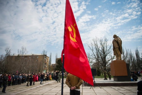 A Soviet Union flag flutters as people attend the unveiling of a Lenin statue in the town of Novoazo